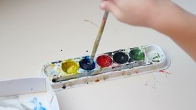 递与水彩的儿童绘画在纸 孩子弄湿在水彩油漆的刷子 股票录像