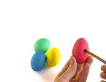 递与油漆刷的绘的复活节彩蛋在白色背景 库存照片