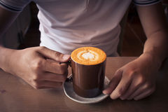 递举行一杯咖啡顶视图表面心脏形状在木背景中 图库摄影