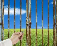 递举行与绿色草甸和天空的关键打开的门 免版税图库摄影