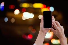 递举行和触摸屏巧妙的电话在抽象bokeh后面 免版税库存照片