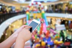 递举行和触摸屏巧妙的电话,在depa被弄脏的照片  免版税库存图片