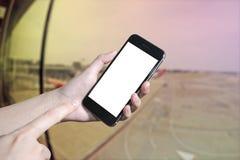 递举行和触摸屏巧妙的电话,片剂,在机场终端货物的手机  免版税库存照片