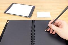 递举行在空白的黑名册的铅笔文字与桌和b 免版税库存照片