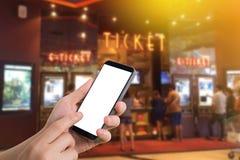 递举行并且接触在模糊的剧院背景的智能手机 库存图片