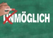 递举行粉笔不可能的改变的词UNMÃ-GLICH德语对可能的MÃ-GLICH德语在黑板 库存图片