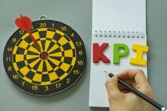 递举行铅笔和五颜六色的字母表与掷镖的圆靶的KPI  库存图片
