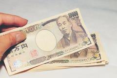 递举行10000日本人货币,票据日元在一个鳄鱼纹理钱包里,在白色背景,拷贝空间 免版税图库摄影