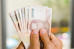 递举行1000泰铢钞票,薪金或存金钱 库存图片