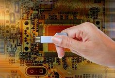 递举行USB数据存储反对光和电路 免版税库存照片