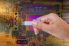 递举行USB数据存储反对明亮的光和电路 免版税库存图片