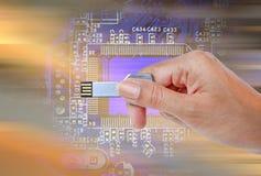 递举行USB数据存储反对明亮的光和电路 免版税图库摄影