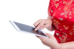 递亚洲女服中国人礼服传统cheongsam或qipao 拿着黑屏数字式片剂的手 图库摄影