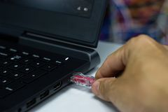 递人连接与膝上型计算机的Lan口岸的红色有线网连接 免版税库存图片