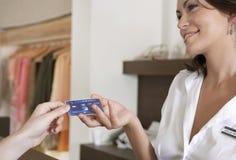 递信用卡的妇女现有量在计数器 库存图片