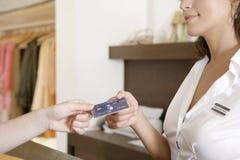 递信用卡的妇女现有量在计数器 库存照片