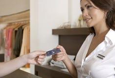 递信用卡的妇女现有量在计数器 免版税图库摄影