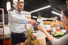 递信用卡的愉快的人对出纳员在超级市场 免版税图库摄影