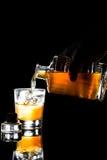 递倾倒一杯在岩石之上的威士忌酒反对黑暗的背景 库存图片