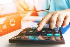 递做财务的人并且在家计算在关于费用办公室的书桌上 定调子 库存图片