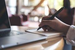 递写下在有膝上型计算机的一个空白的笔记本在木桌上 免版税库存照片