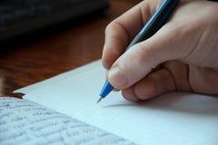 递写笔在习字簿,文字的过程 免版税图库摄影