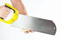 递削减与一把手锯的一个木块在白色背景 免版税库存图片