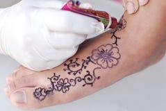 递图画在一只脚的无刺指甲花艺术有白色背景 免版税库存照片