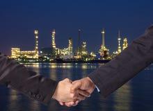 递在一个商人之间的震动在石油化学的工厂backgr 免版税库存照片
