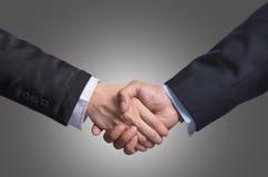递在一个商人和一名女实业家之间的震动灰色bac的 免版税库存照片