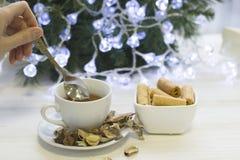 递在一个白色杯子的混乱茶有茶碟的,碗曲奇饼,在后面的圣诞节树 图库摄影
