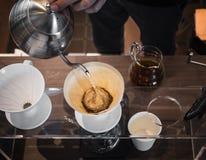 递在咖啡渣的滴水咖啡Barista倾吐的水与过滤器 免版税图库摄影