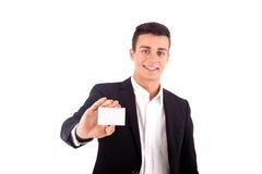 递在白色后面的年轻商人一张空白的名片 库存图片