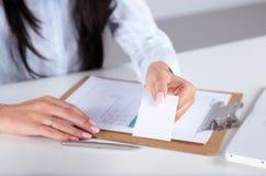 递在白色背景的微笑的女商人一个空插件 免版税库存图片