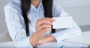 递在白色背景的微笑的女商人一个空插件 图库摄影