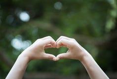 递在脱口说出自然式铃声的心形的bokeh背景的表示 向您爱家庭爱之间的世界显示 库存照片