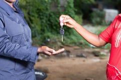 递她的汽车的钥匙少妇对技工 免版税库存照片