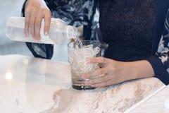 递妇女从透明塑料饮用的马胃蝇蛆的纯净的自来水 库存图片