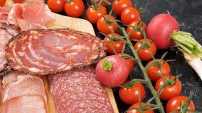 递安置西红柿和萝卜在板材whith切的火腿和烟肉旁边 股票视频