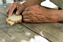 递恶劣的老人` s,面包片和变动,在木背景的便士 库存照片