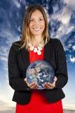 递您的世界 微笑与地球的妇女在手上 免版税图库摄影