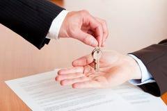 递房子关键字的生意人汽车  免版税库存图片