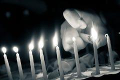 递打开生日蛋糕的蜡烛与打火机 免版税库存图片