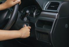 递把握汽车关键的妇女司机并且发动有现代汽车的引擎 免版税库存图片