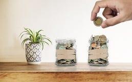递把硬币放在玻璃瓶,有装饰植物的在木书桌上,保存的金钱,投资并且节约概念 免版税库存图片