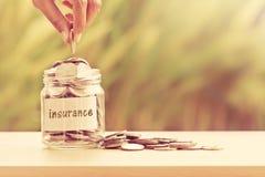 递投入硬币在节约金钱保险conce的玻璃瓶子 库存照片