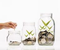 递投入金黄硬币并且播种在白色背景的清楚的瓶子 免版税库存照片