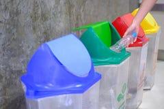 递投掷的空的塑料瓶入垃圾 免版税库存图片