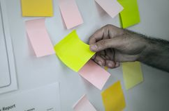 递拉扯提示张贴的便条纸在委员会外面 免版税库存照片