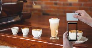 递拍摄杯子与巧妙的电话的热奶咖啡,当拿着在咖啡店时的卡片 库存照片
